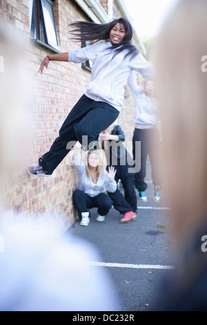 Teenage girl dancing against brick wall - Stock Photo
