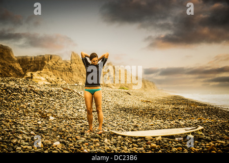 Young woman standing on pebble beach looking down at surfboard - Stock Photo