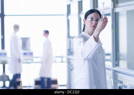 Chemistry student looking at flask in laboratory - Stock Photo