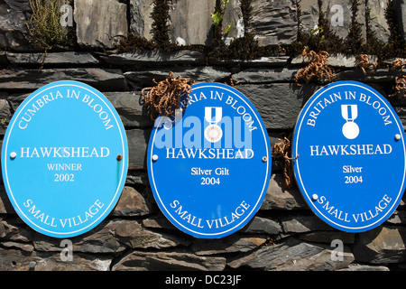 Plaques on a wall in the Beautiful Lakeland village of Hawkshead showing  success in Cumbria  and Britain in bloom - Stock Photo