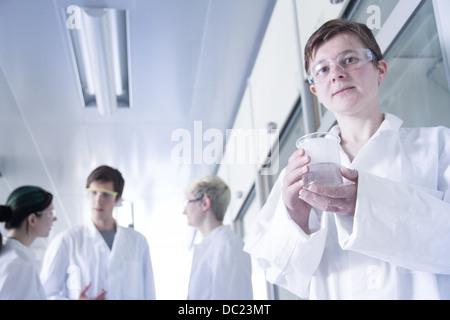 Chemistry student holding beaker in laboratory, portrait - Stock Photo