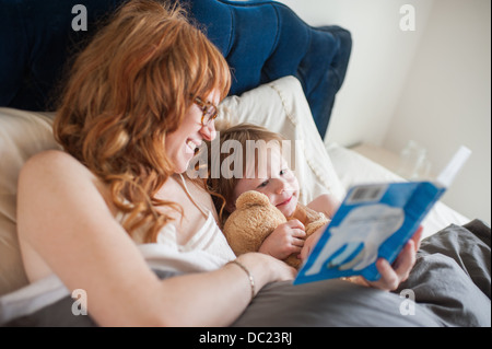 Mother and daughter reading book lying in bed - Stock Photo