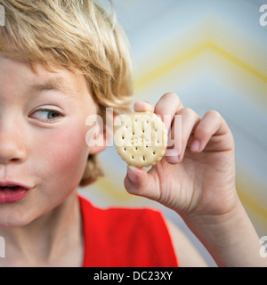 Boy holding cool biscuit - Stock Photo