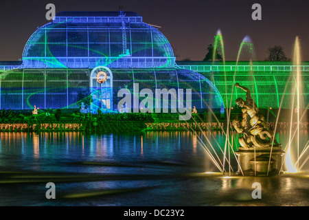 Christmas lights display at Royal Botanic Gardens, Kew, London, England, featuring the iconic Palm House and Pond. - Stock Photo