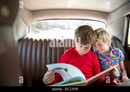 Boys sitting in back of car reading book - Stock Photo