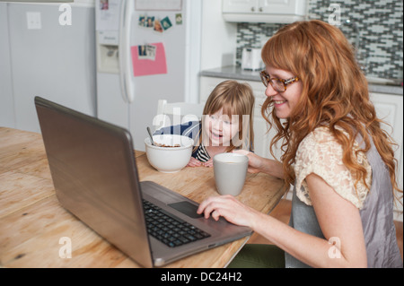 Mother and daughter having breakfast and using laptop - Stock Photo