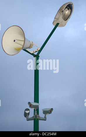 Isolated Green Pole with Grey Lamp, White Loudspeaker and Grey Security Cameras - Stock Photo