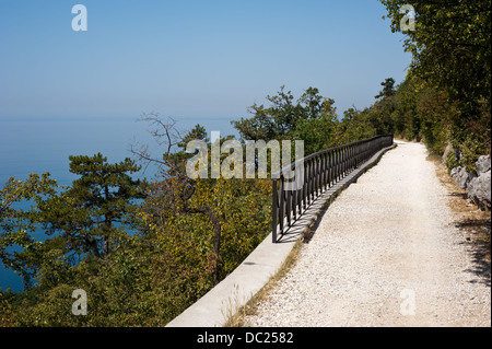 An elevated sun-drenched trail facing the ble sea. Taken on the via Napoleonica in Trieste, Italy - Stock Photo