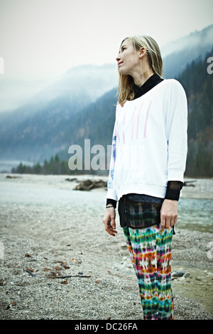 Hippy woman standing in mountains - Stock Photo