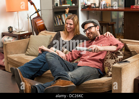 Couple sitting on sofa watching television - Stock Photo
