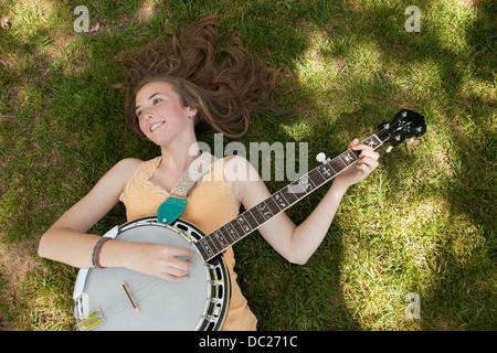 Teenage girl playing banjo on grass, overhead view - Stock Photo
