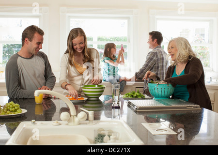 Three generation family in kitchen preparing food - Stock Photo
