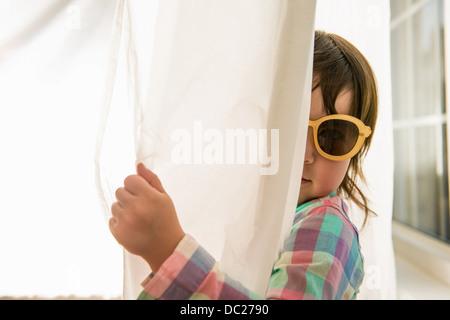 Girl peering round curtain wearing sunglasses - Stock Photo