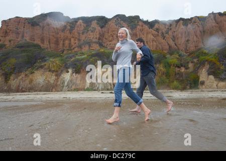Mature couple running on beach - Stock Photo