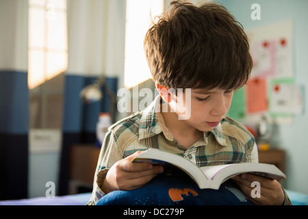 Boy sitting on bed reading book - Stock Photo