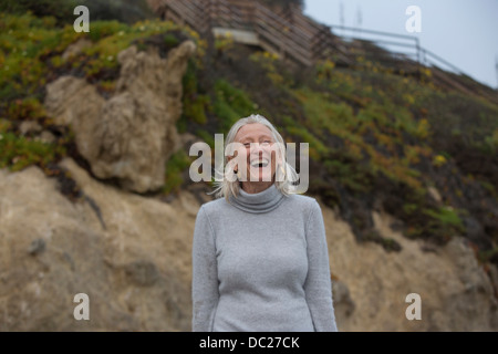 Mature woman laughing on beach - Stock Photo