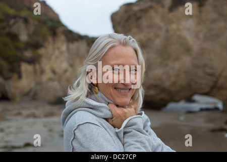 Mature woman wearing grey sweater on beach, smiling - Stock Photo