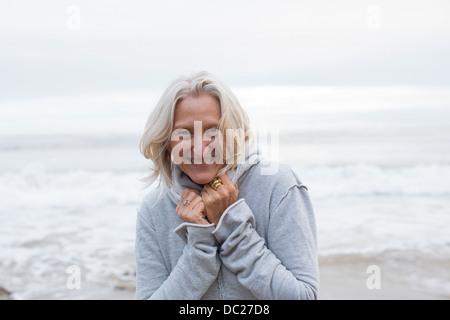 Mature woman wearing grey sweater on beach, smiling - Stock Photo
