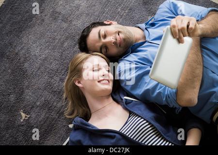 Young couple lying on floor with electronic book - Stock Photo