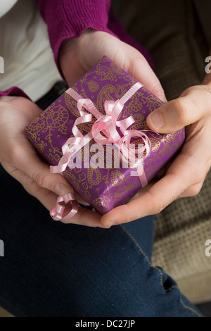 Two people holding gift box with pink ribbon - Stock Photo