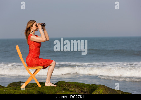 Mature woman sitting on chair on beach with binoculars - Stock Photo