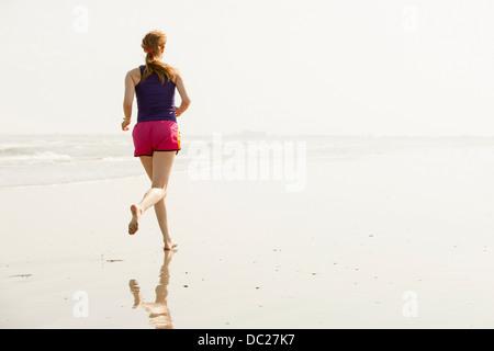 Mature woman jogging on beach - Stock Photo