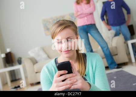 Teenage girl using cell phone, parents in background - Stock Photo