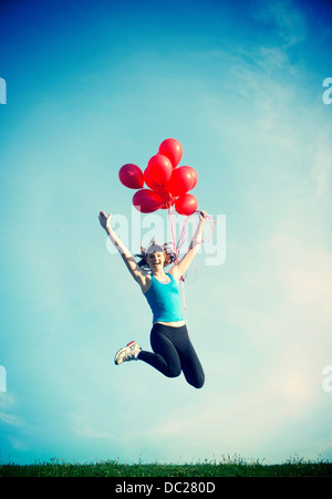Teenage girl jumping in mid air holding red balloons - Stock Photo