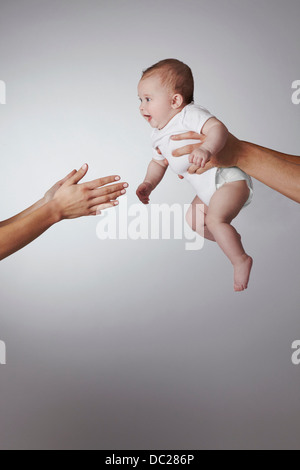 Parents passing baby daughter to each other - Stock Photo