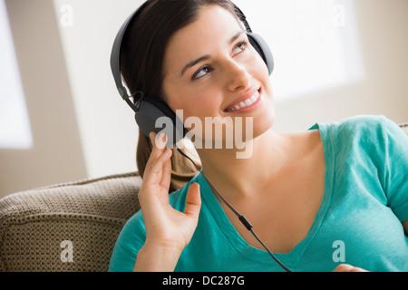 Young woman wearing headphones - Stock Photo