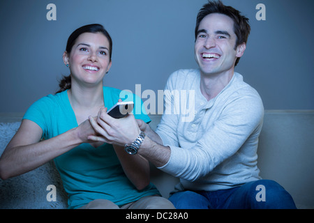 Couple watching television, fighting over remote control - Stock Photo