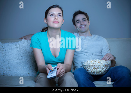 Couple watching television with popcorn - Stock Photo