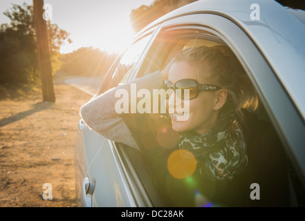 Woman looking out of car window - Stock Photo