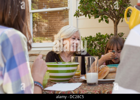 Family having breakfast outdoors - Stock Photo