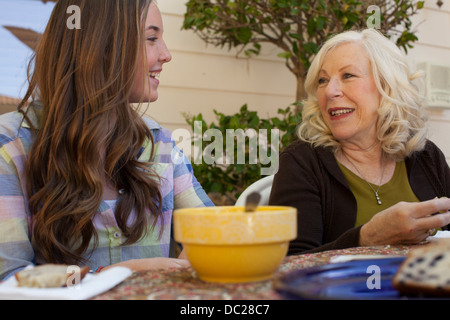 Grandmother and granddaughter having breakfast outdoors - Stock Photo
