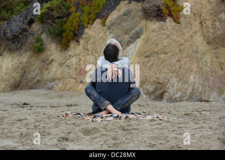 Mature couple sitting on beach cross legged, rear view - Stock Photo