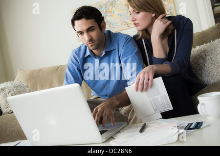 Young couple paying bills online - Stock Photo