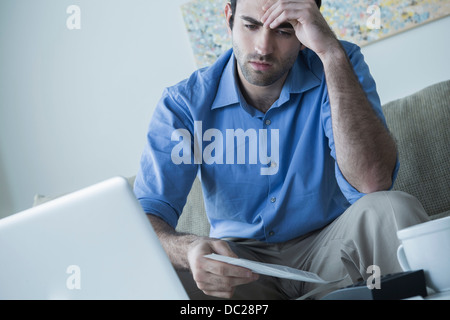 Worried man with hand on head holding bills - Stock Photo
