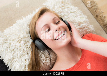 Teenage girl wearing headphones with eyes closed - Stock Photo