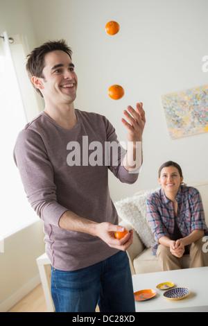 Man juggling oranges, woman watching - Stock Photo
