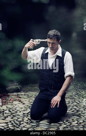 a man in vintage clothes is sitting on the ground, trying to shoot himself - Stock Photo
