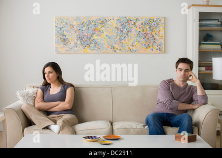 Couple sitting on sofa ignoring each other - Stock Photo