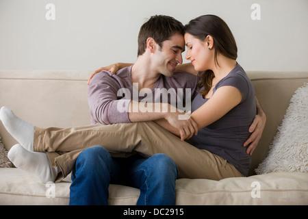 Couple on sofa, woman sitting on man's lap