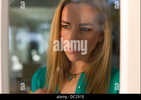 Portrait of young woman looking out of window - Stock Photo