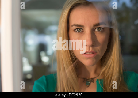 Portrait of young woman staring through window - Stock Photo