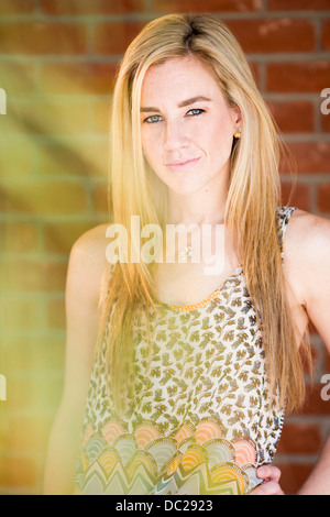 Portrait of young woman with long blonde hair wearing patterned top - Stock Photo