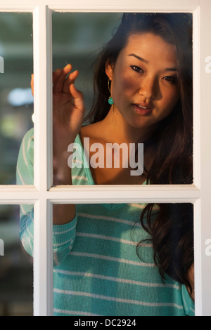 Portrait of young woman looking through window - Stock Photo