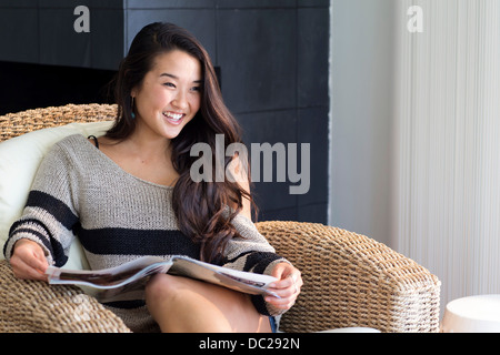 Portrait of young woman sitting on armchair with magazine - Stock Photo