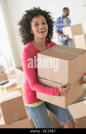 Mid adult woman carrying cardboard boxes - Stock Photo