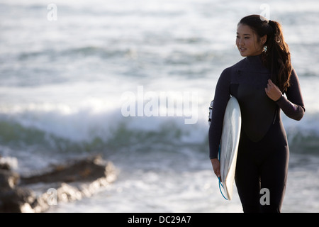 Young woman wearing wetsuit with surfboard - Stock Photo